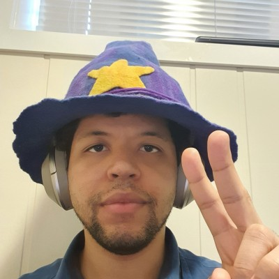 Photo of Kevin Kaland (wizonesolutions) wearing his wizard hat giving a peace sign.