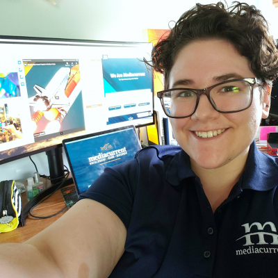 A selfie of a young woman with short curly hair and a navy blue Mediacurrent branded polo. In the background is a laptop and monitor open to DrupalCon, CelebrateDrupal.org, and Mediacurrent.com