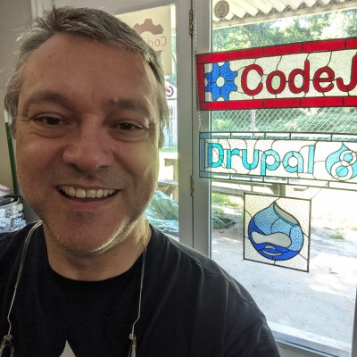 Drupal selfie with Drupal logos in background