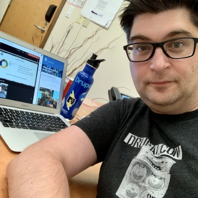 Selfie of a man wearing a DrupalCon shirt in front of a laptop displaying DrupalCon content