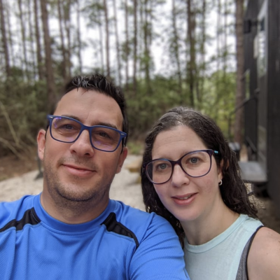 Carlos and Me with a background of trees and a cabin
